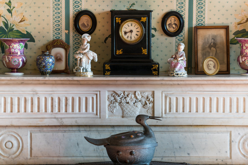 Carved marble mantel from Italy. Oval framed photographic print (at right, in front of another framed image): Robert E. Lee in military uniform, late 19th-c copy. Lee was a first cousin by marriage of Britannia Peter Kennon, the home's second owner, whose bedroom this was. Clock, ebonized wood, by Bradely and Hubbard, West Meridian Connecticut; c. 1890