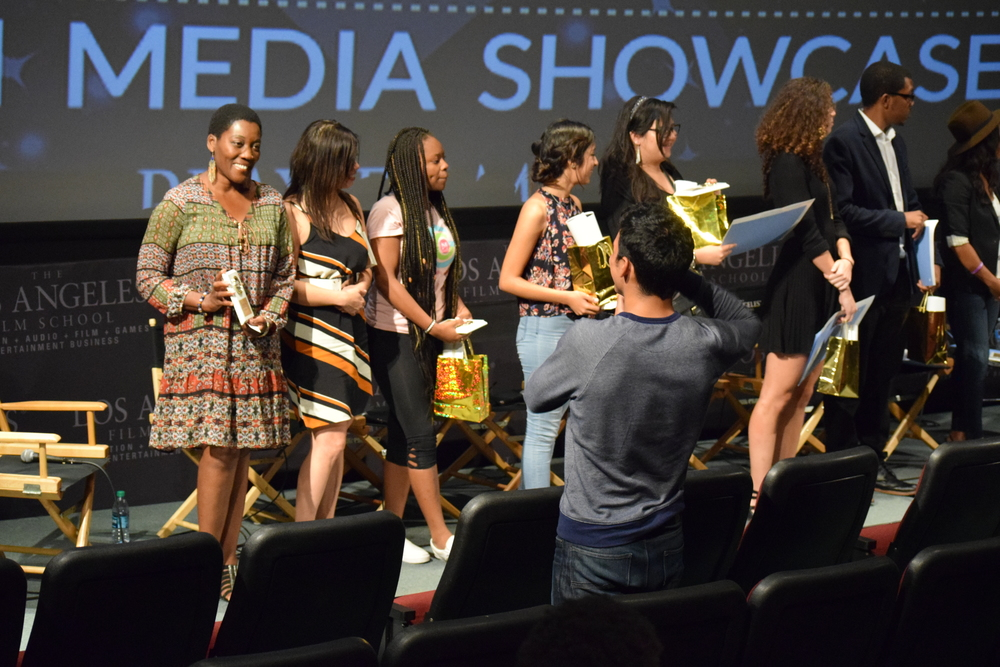 AKUYOE GRAHAM RECEIVES A SERVICE AWARD FROM REAL TO REEL MEDIA SHOWCASE.
