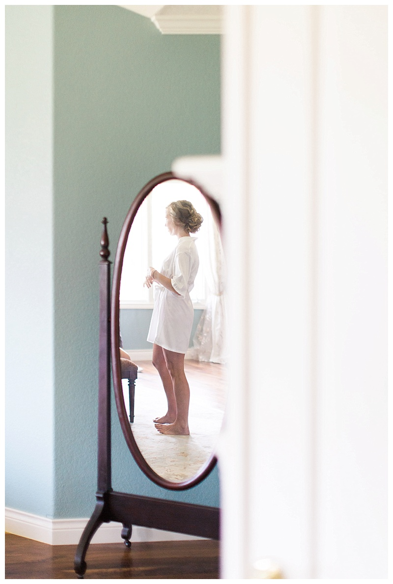 Bride getting ready through antique mirror