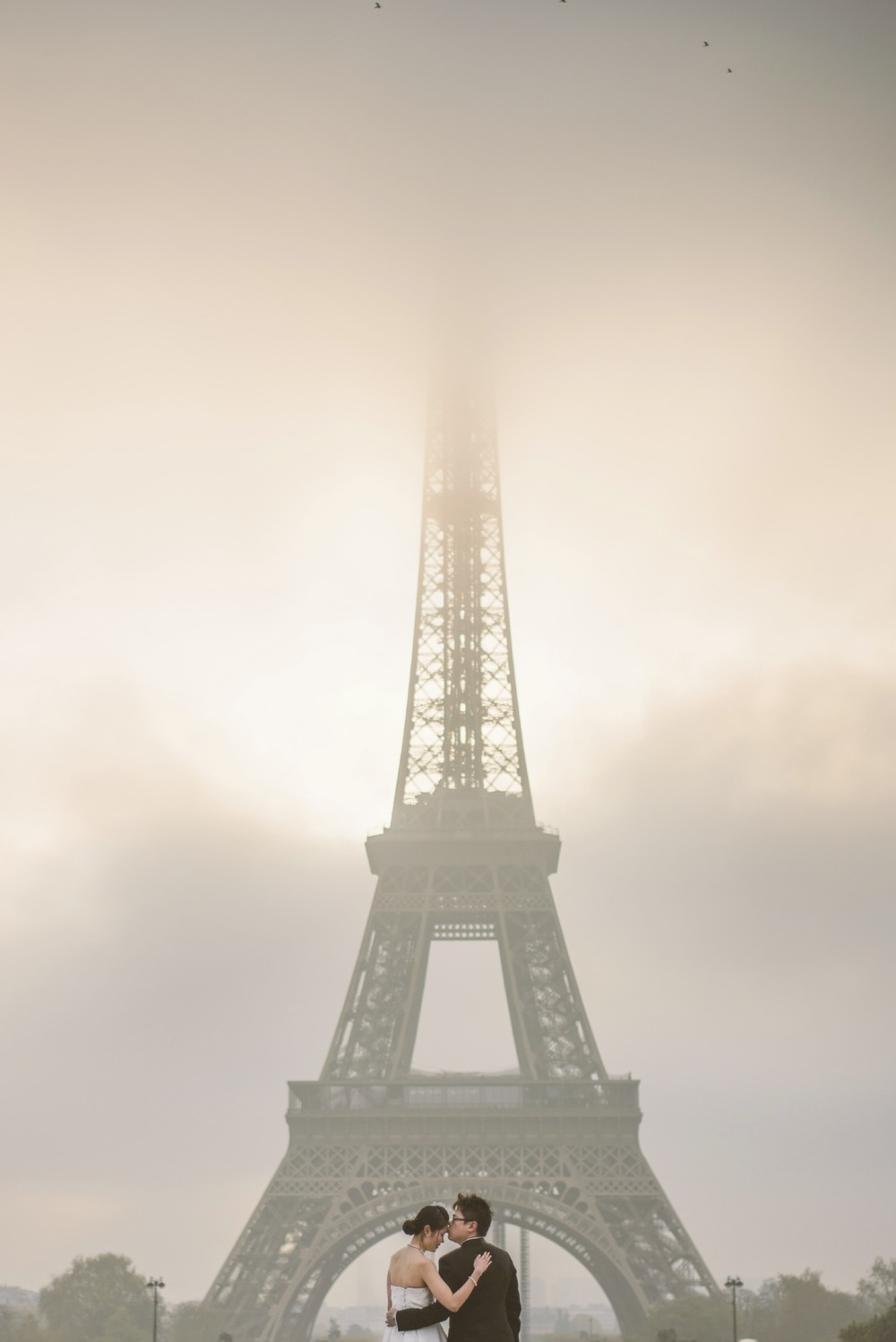 Couple kissing in front of the foggy Eiffel Tower