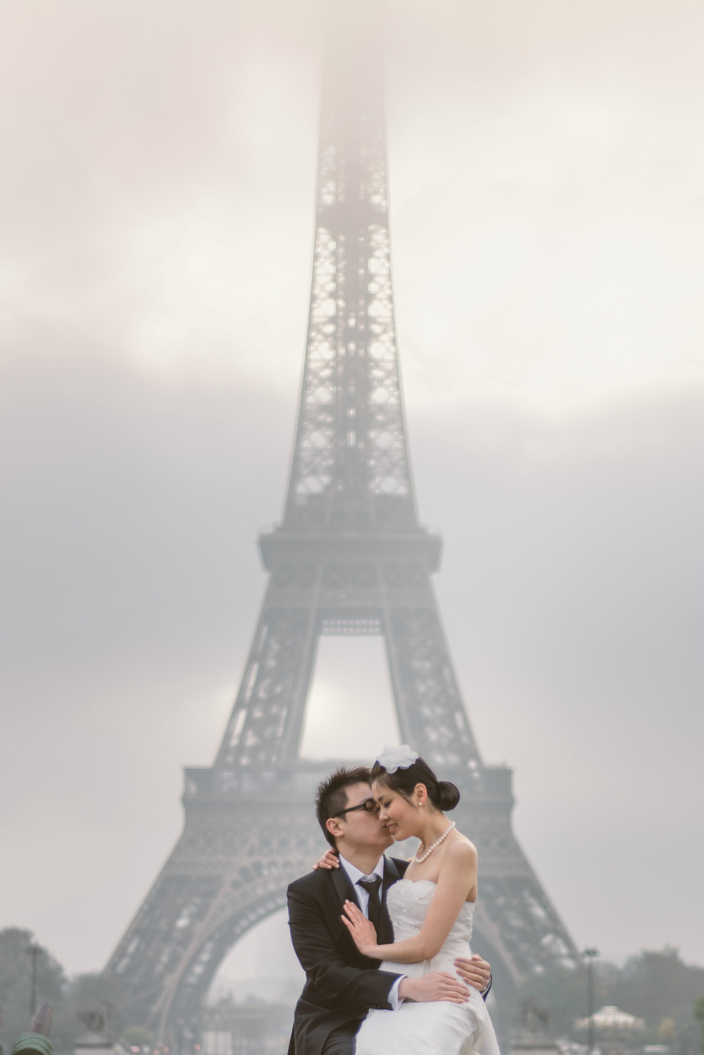 Prewedding session in Paris couple kissing in front of the foggy Eiffel Tower
