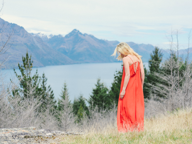Red dress girl on top of the mountains with a view on Lake Queenstown