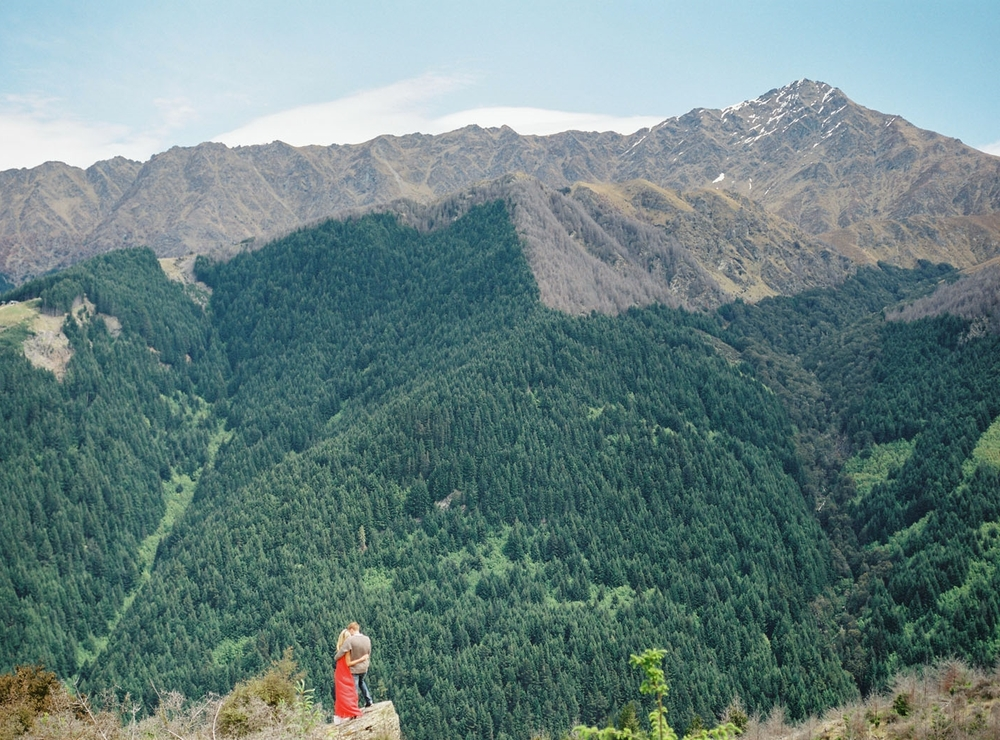 Epic picture of couple on top of Queenstown hill in New Zealand with red dress