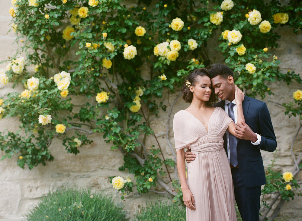 Beautiful black bride and groom in front of roses