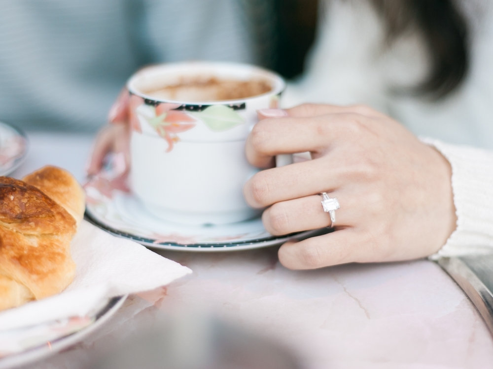 Engagement ring with coffee and croissant in Paris