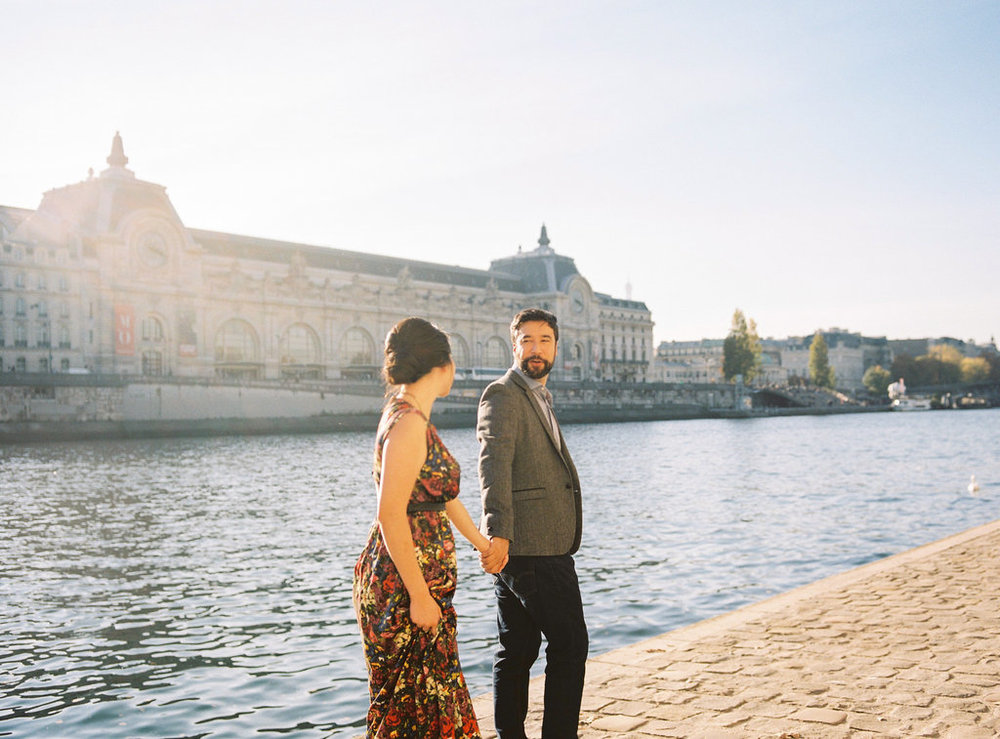 Couple holding hands by river Seine Paris