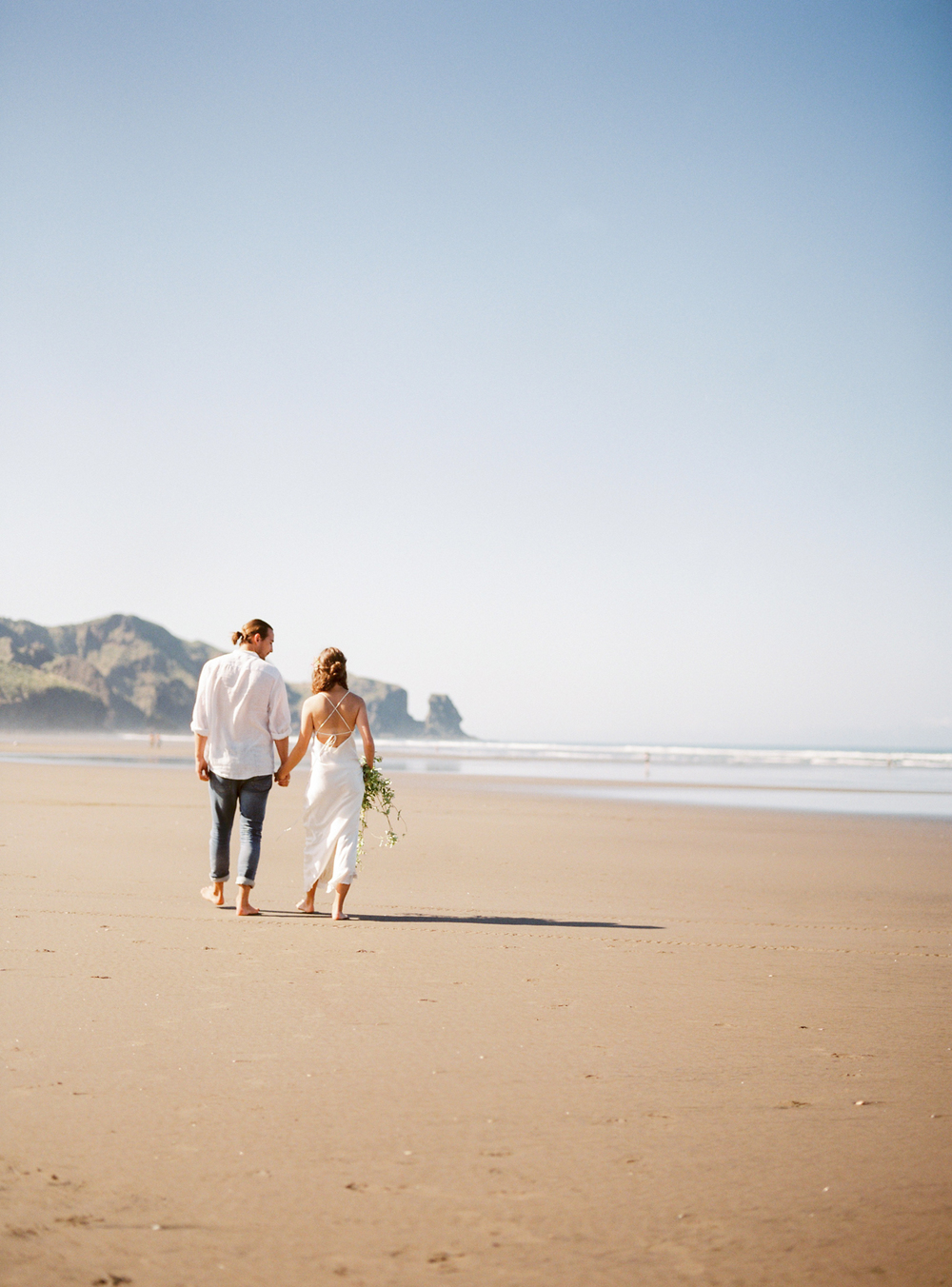 Couple walking down the beach in New Zealand elopement