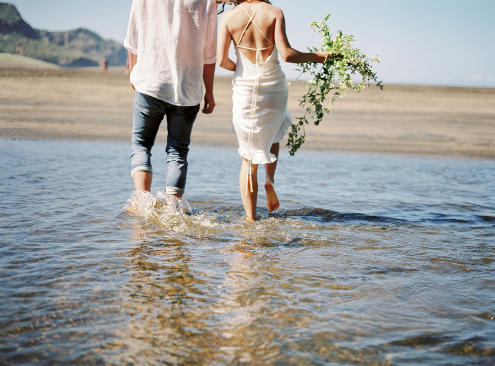 Couple walking in the water for wedding in New Zealand