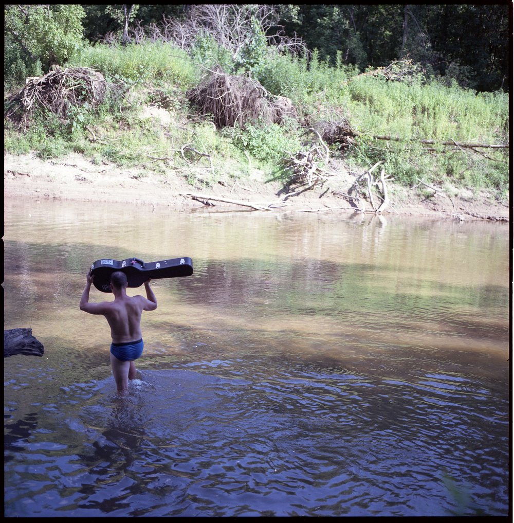 Drew fording the river to give Matt his Gibson.