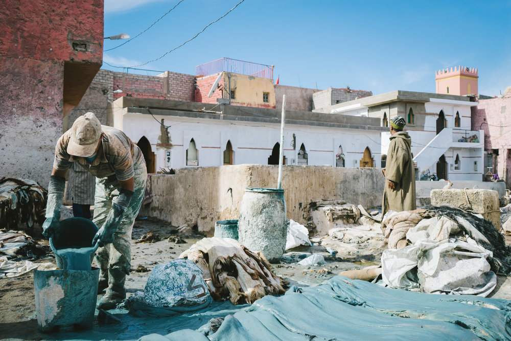 A tannery worker in Marrakech's Medina works hard in the mid day sun