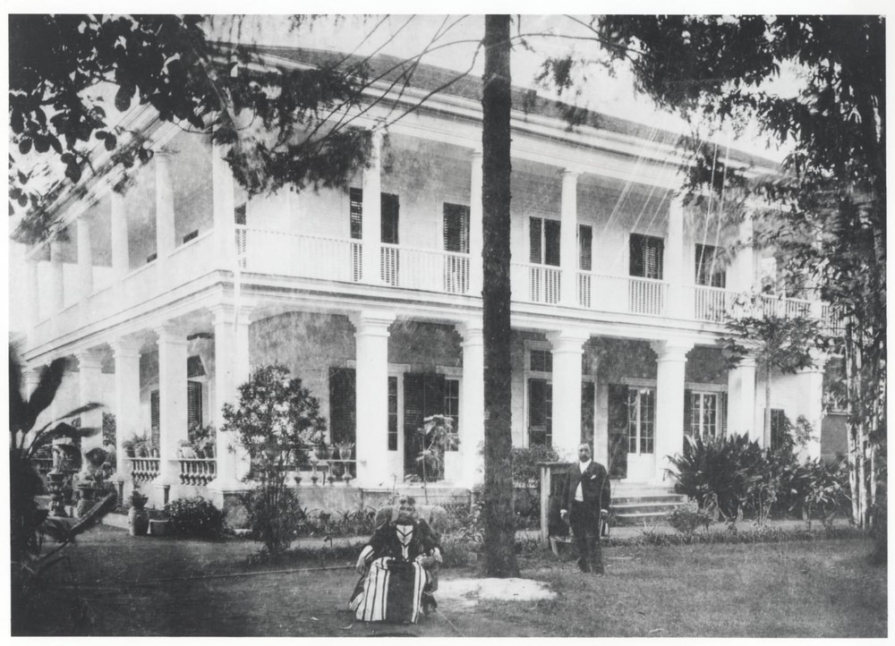 Queen sitting on the front lawn.   Hawaii State Archives