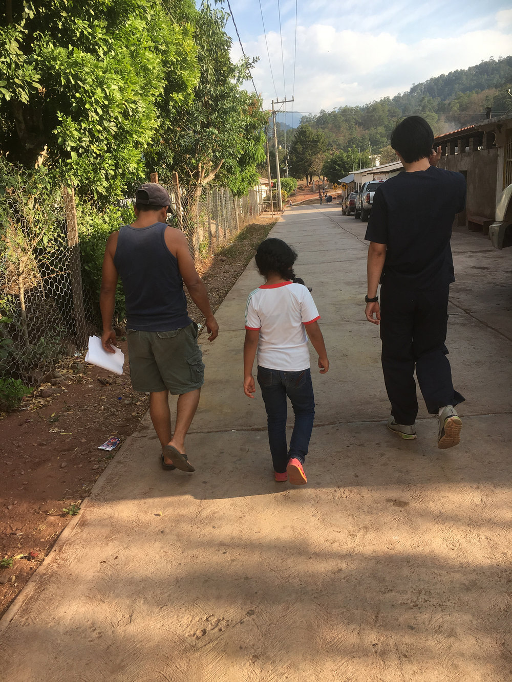 El Dr. Iván Martínez camina de vuelta a la clínica con un padre y su hija mientras platican sobre la enfermedad de uno de ellos. Las consultas de improviso son comunes.