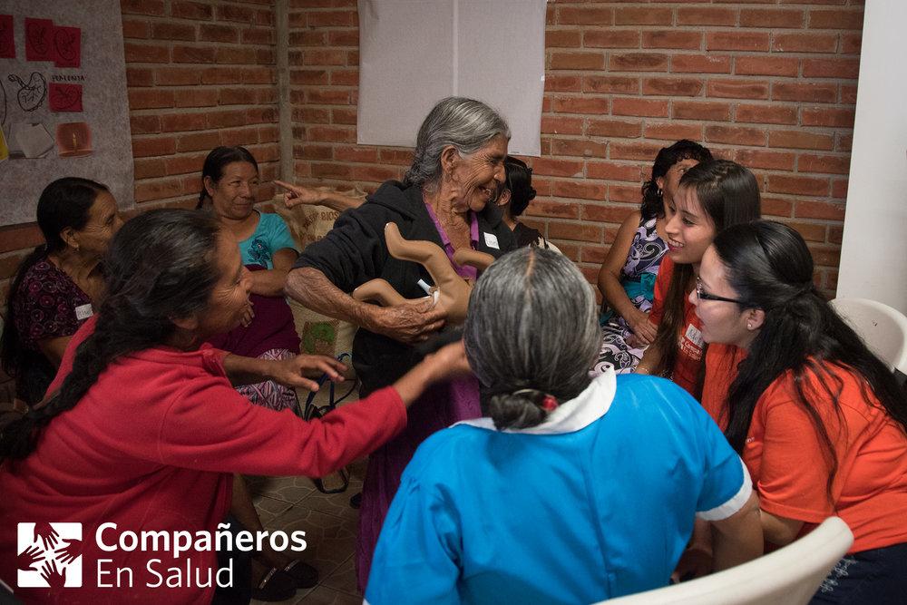 Parteras tradicionales intercambiando experiencias con los pasantes de la licenciatura en efermería y obstetricia durante una capacitación.