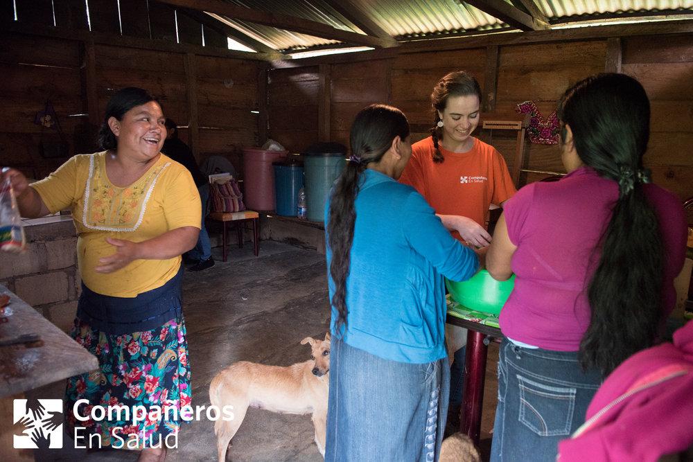 Convivencia entre Nati (Natividad) Hernández Vázquez, Irma Cifuentes Matías, y Eva Díaz Morales (participantes de un taller de la clínica)en la cual dan la bienvenida a la voluntaria Sarah Hartman en su cocina y le enseñan cómo hacer tamales.