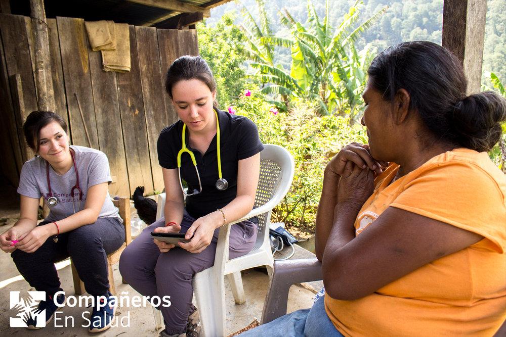 Nuestros médicos de las clínicas comunitarias y su supervisores clínicos participan también en esta experiencia de aprendizaje para los estudiantes de medicina.  Foto: La Dra. Fátima Rodríguez (izquierda), supervisora clínica en Compañeros En Salud, acompaña a Andrea Rodríguez, estudiante de medicina, durante una encuesta en la casa de Doña Evitelia (derecha) en la comunidad Concepción Pinada.Foto por Rodrigo Noguez Tamayo