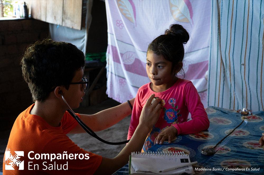 Durante las encuestas para los niños, evaluamos el riesgo que tienen de padecer enfermedades como asma o desnutrición.  Foto: Armando Osorio Salazar, estudiante de medicina, escucha los latidos del corazón de Ximena durante las encuestas de salud de su familia.
