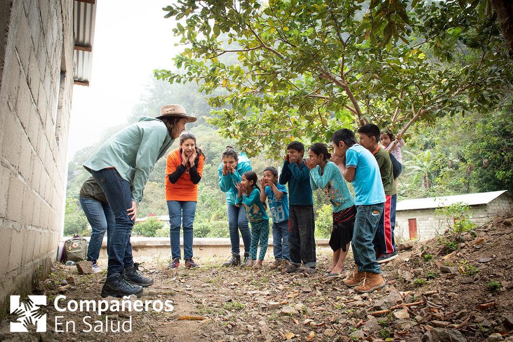 Foto: Los estudiantes de medicina lideran un juego con los niños después de sus encuestas, mientras su compañera termina la última encuesta en esa parte de la zona.