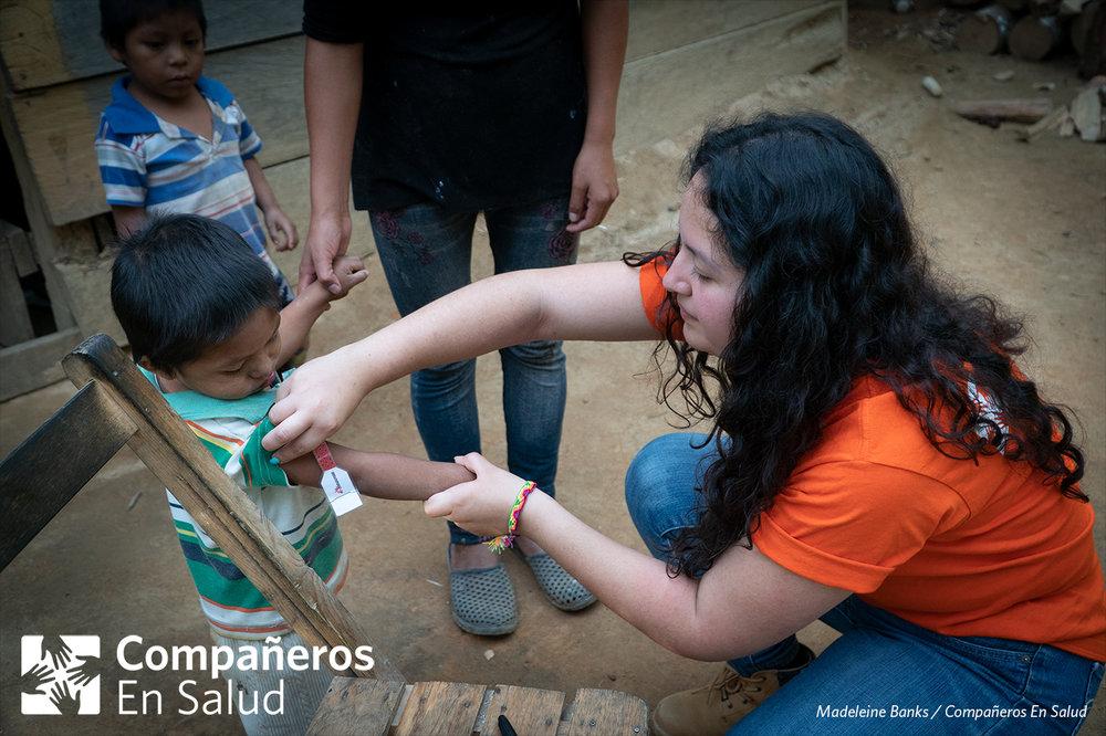 Foto: Berenice Morales Montoya, estudiante de medicina, mide el tamaño del brazo de Elimquer como parte del proceso de evaluar el riesgo de desnutrición.