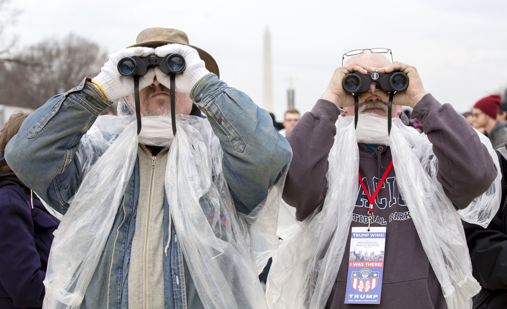 "Dean Keppler, left, and Mark Koons, of Muncie, IN, use binoculars to get a better view of the capital as Donald Trump is sworn in as the 45th president. Keppler voted for Gary Johnson because he believed he was the better option between Trump and Clinton. Koons voted for Trump and he says he is ""cautiously optimistic"" that Trump will bring change."