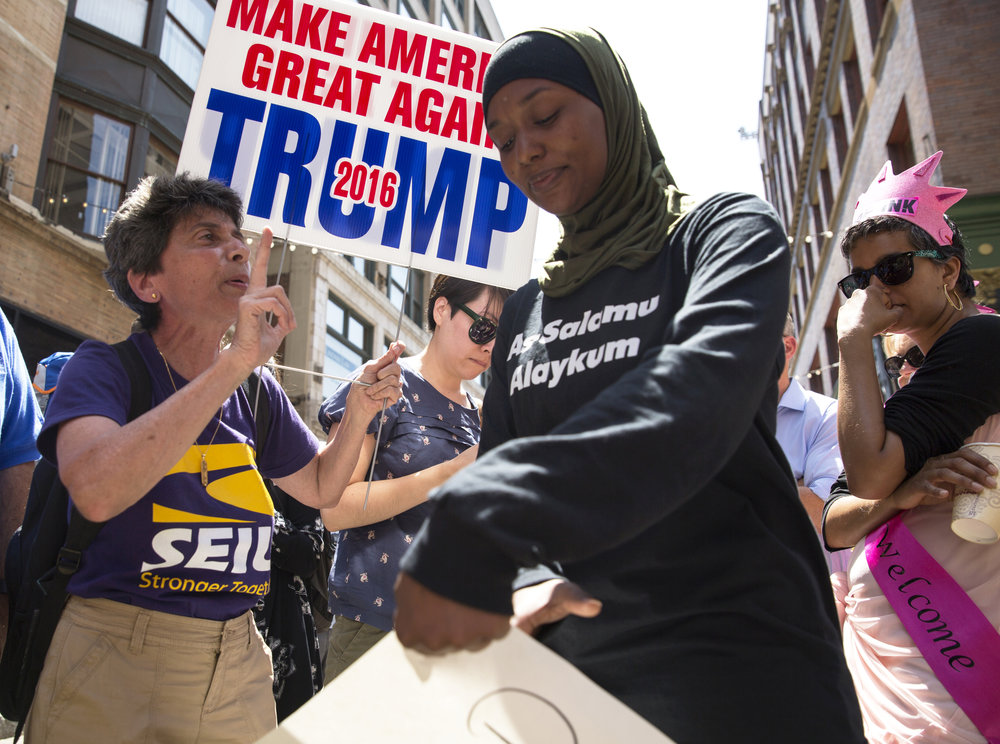 "Mariam Noujaim, 62, who is from Egypt, left, tries to make a point about immigration with Desiree Hoy, of Detroit, Mich., on East 4th Street in Cleveland, on the third day of the Republican National Convention on Wednesday, July 20, 2016. Hoy's shirt bears a Muslim greeting written in Arabic, ""Peace Be Upon You."""