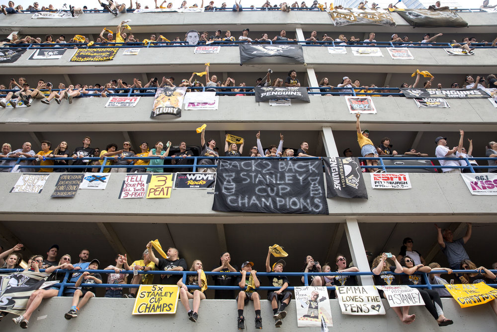 Fans occupy as much space as they can in the Allies Garage in downtown Pittsburgh as they cheer on the Penguins players during the victory parade on Wednesday, June 14, 2017. The Penguins defeated the Predators 2-0 in the Stanley Cup Final during game 6.