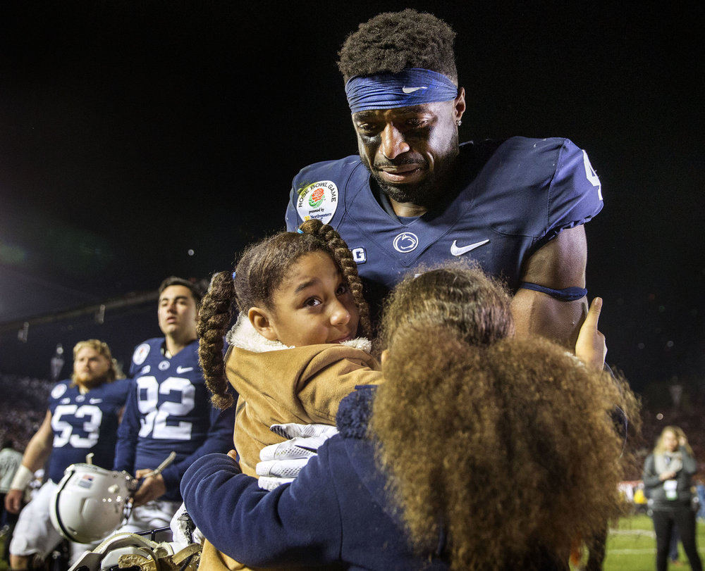 Addy and Shola Franklin hug Penn State's Nick Scott after USC defeated the Nittany Lions 52-49 in the Rose Bowl game in Pasadena, CA on Monday, Jan. 2, 2017.