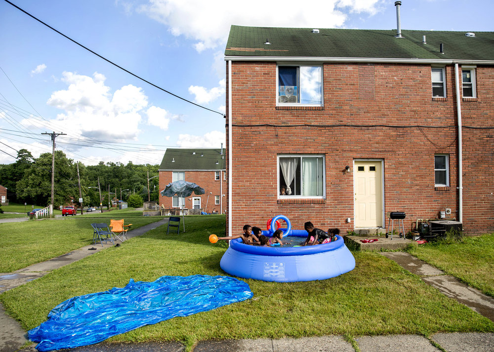 Jemarcus Compton, 12, of Clairton, stretches his arm out to keep posession of the ball while playing with friends in an inflatable pool on Monday, June 4, 2018 at the Century Townhomes in Clairton. Several hundred residents of the Century Townhomes lost tap water for about six hours amost a month ago but it is the third time in four years that residents in the complex have had their water shut off.