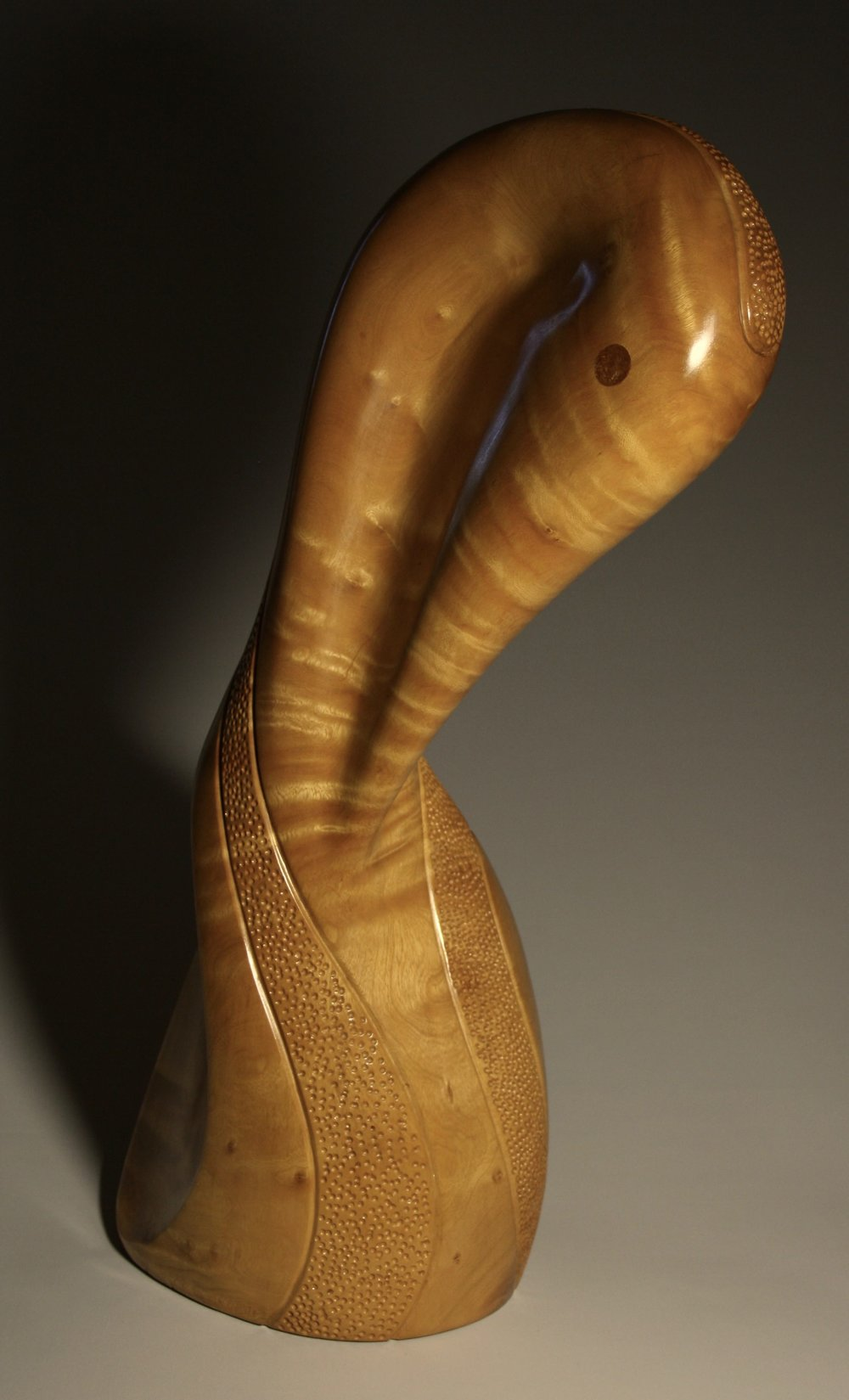 'Pelican Preening'     Dimensions:  72x45x25cm   Wood:  Jacaranda   Artist Statement:  I have always been taken by how birds can manage to twist their necks and reach nearly all parts of their body and delicately preen each feather and look immaculate. By careful orientation I was able to align the beautiful markings in the grain to give the illusion of layers of feathers.