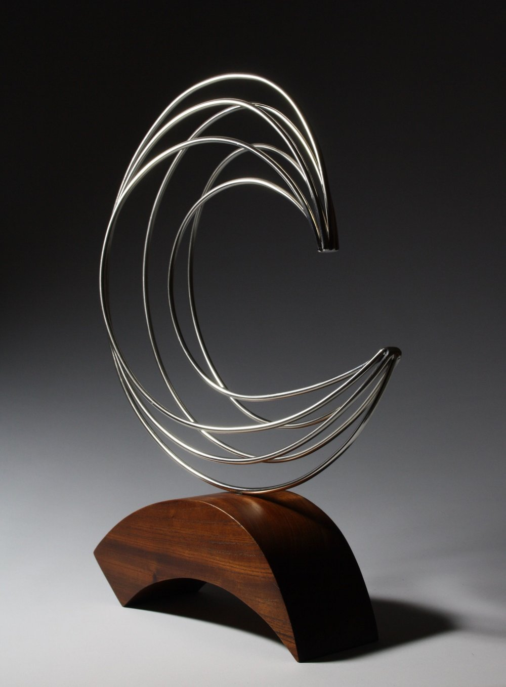 'Breaking Waves'     Dimensions:  52x40x20cm   Wood:  Cedar and Stainless Steel   Artist Statement:  The inspiration of this sculpture came from looking at a clam shell with its curved radial lines, which when you study the clam has lines on the outside in the shape of a wave.