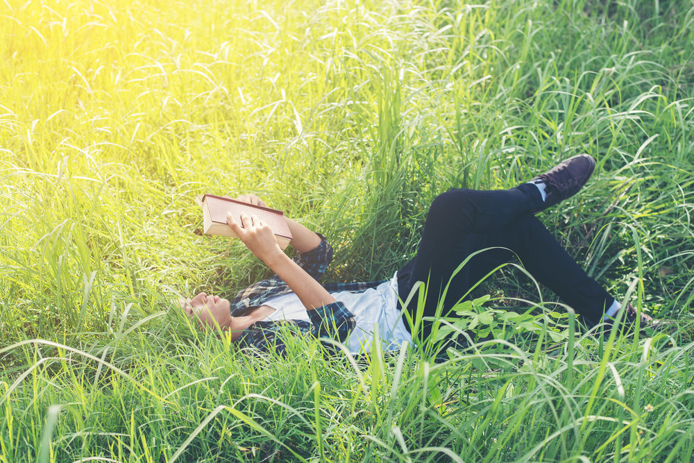 Young hipster man lying down and reading book on grassland.