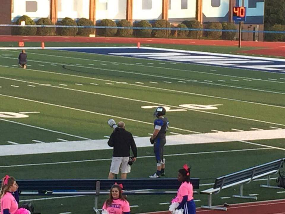 Millikin University football player Connor Brewer stands alone during the national anthem. Photo by Jeff Hill