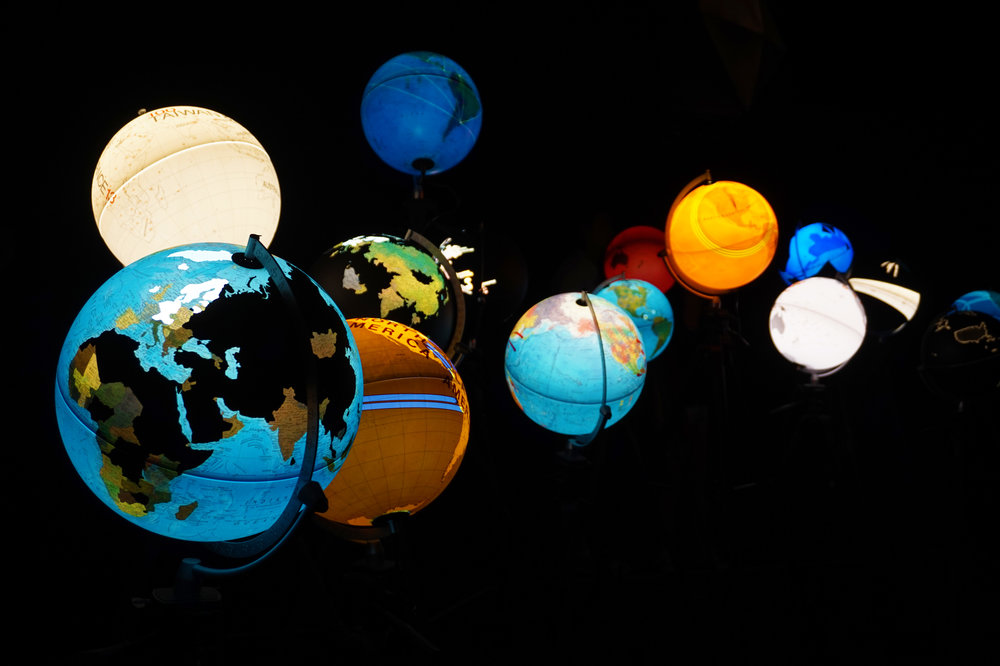 Globes displaying different data sets, like internet freedom, prison population, biggest corporations, and journalistic coverage