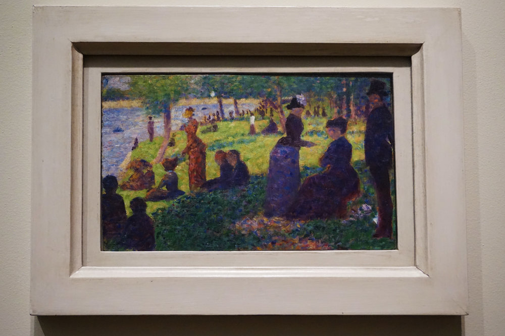 """This small oil on a thin wood panel is one of 24 painted studies Georges Seurat made while conceiving the large, celebrated painting  A Sunday on La Grande Jatte  ... Although at first the panel seems close to the larger canvas, its 20 or more figures have little to do with the final composition. The trio at right, for example, with the elderly seated figure, was completely rethought in the final composition, in which a man in a top hat and a woman walking a monkey convey a sense of grand solemnity and wry humor—a sophisticated irony that is completely absent in the clumsily positioned figures of the oil panel."""