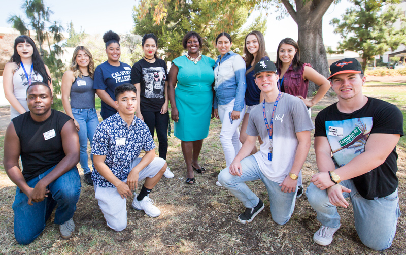 The new Guardian Scholars at Cal State Fullerton are gathered around Berenecea Johnson Eanes, center, vice president for student affairs.