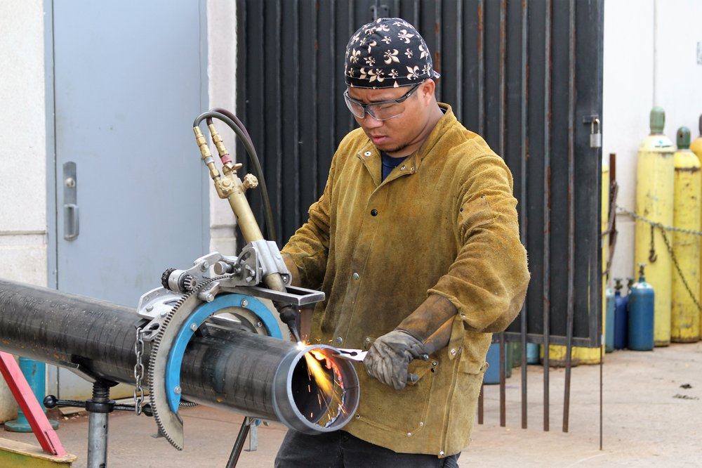 El Centro College student San Awng, who is working with an oxy-fuel gas cutter.