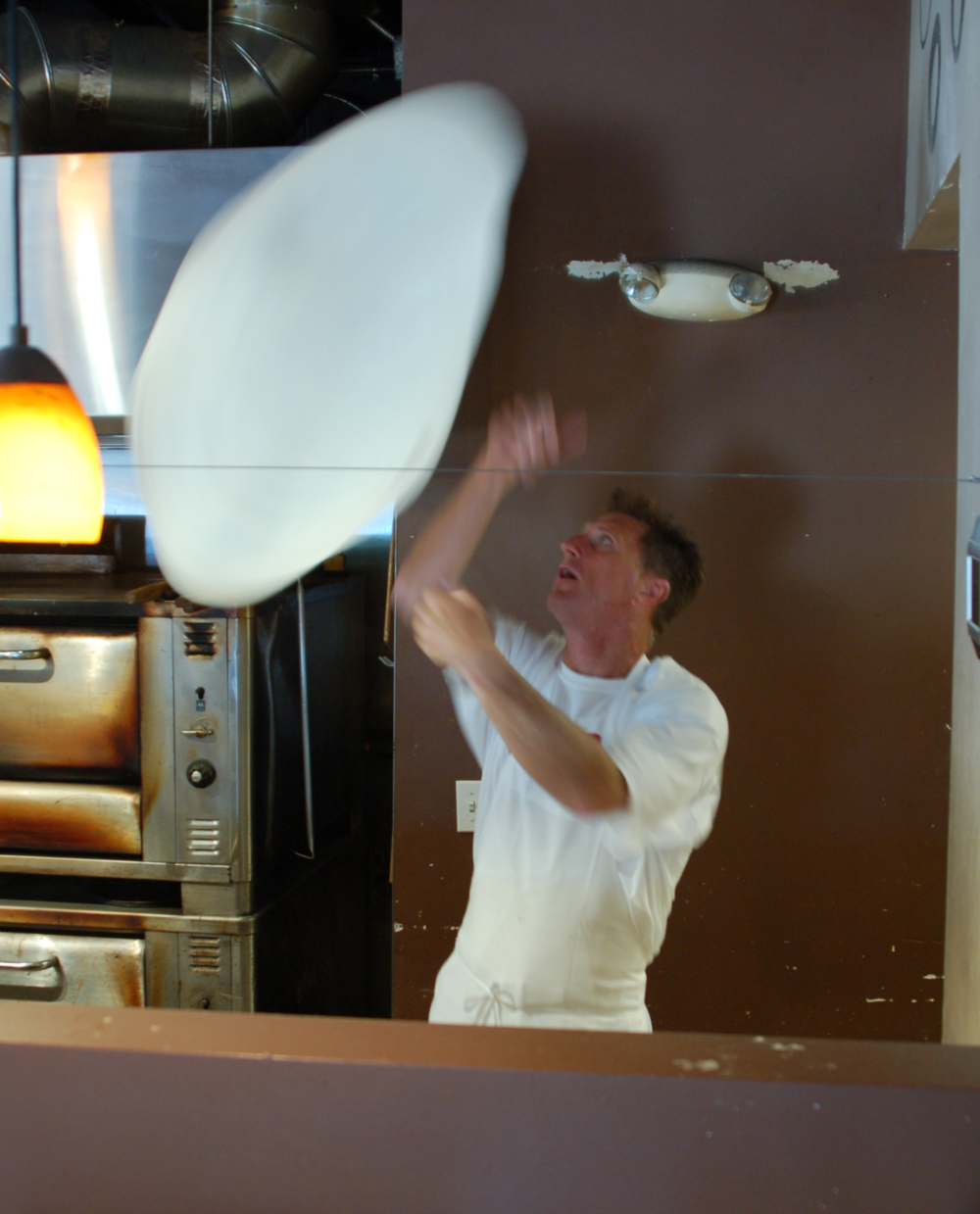 "Here Dan is shown hand-tossing dough for an 18"" pie!"