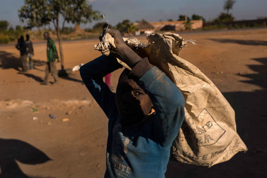 A boy carries a bag used to transport cobalt-laden dirt and rock at the Musompo market.  Credit Michael Robinson Chavez