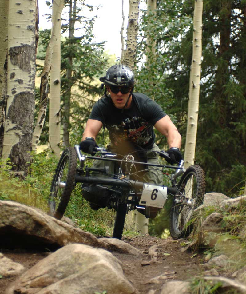 The Handcycle has two wheels in front and one in the back, and the rider rests on their knees and on a chest support. Image from the One-Off Handcycles website.