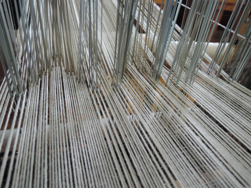 Here's a glimpse at the threading pattern through the heddles on eight different harnesses.  This is what makes the pattern possible!