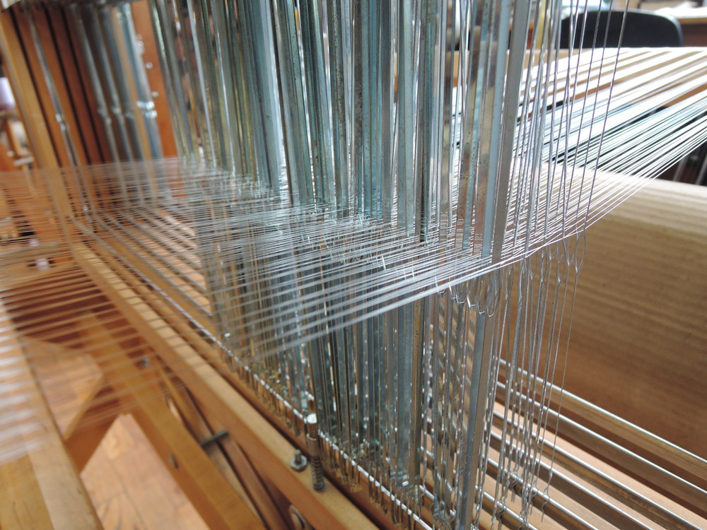 Tiny little strands all happily organized through the heddles.