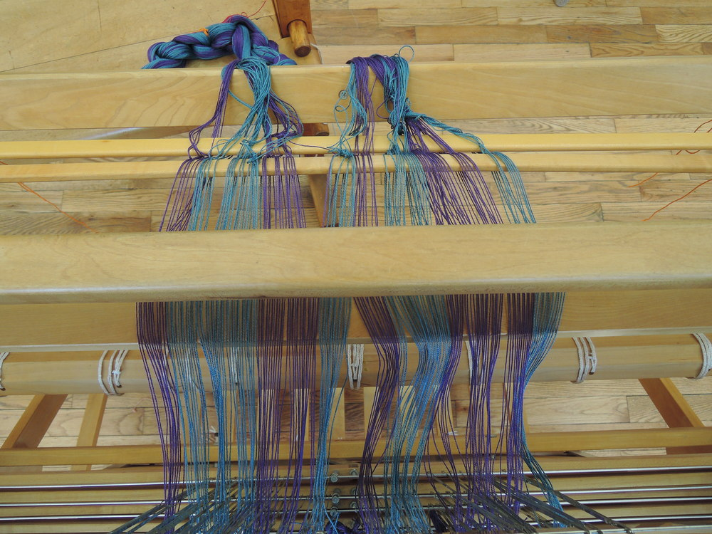 Warp is threaded through the reed and heddles.