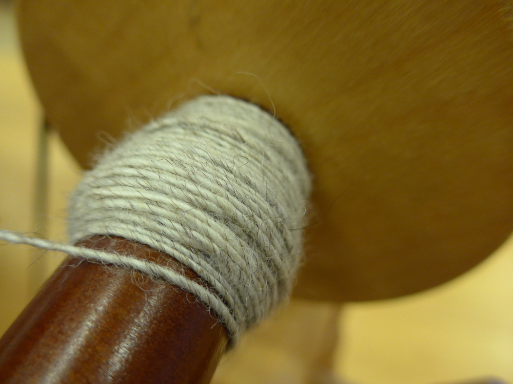 Spinning the fine yarn for the weaving with Greta's fleece.