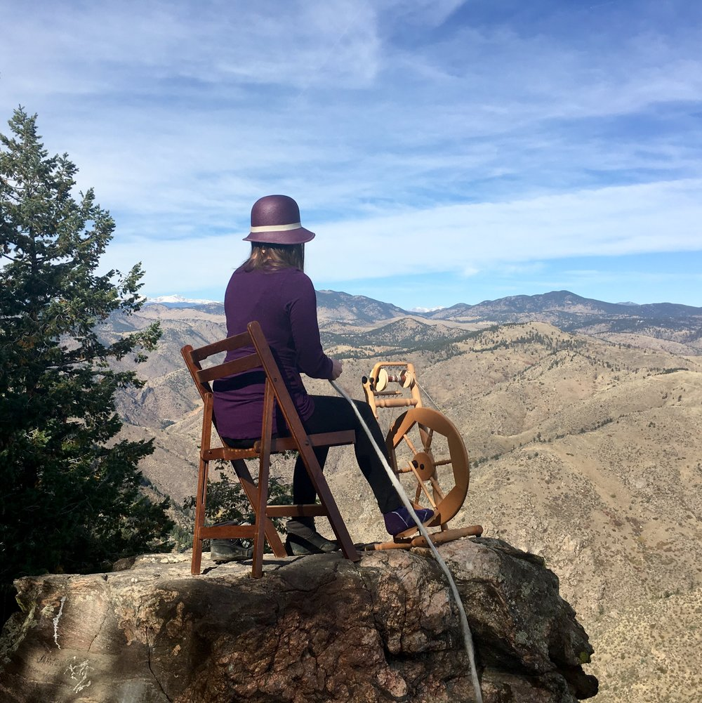 Precariously spinning yarn on a boulder overlooking the Rocky Mountains.