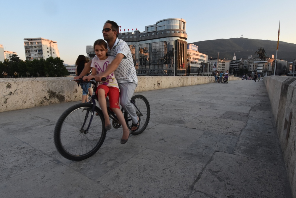 Father and daughter ride their bike across a bridge in Skopje, Macedonia