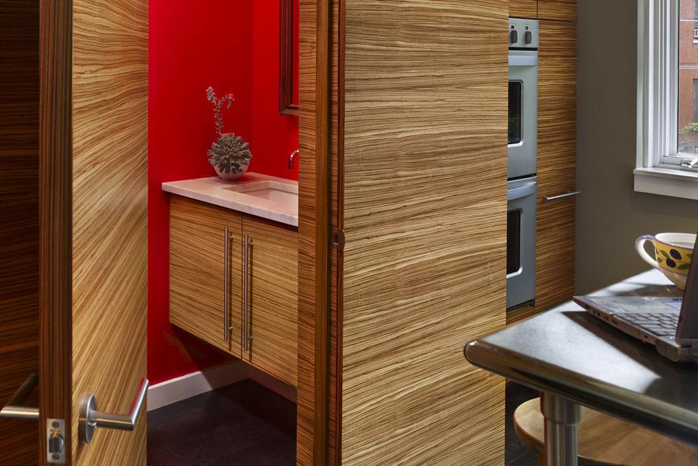 The first floor powder room is hidden behind a beautifully designed wooden door.