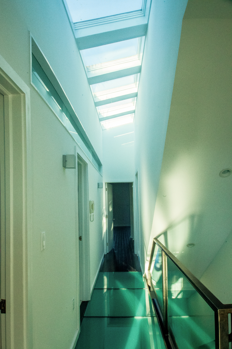The staircase allows light in from the skylight above, through the third floor glass hallway floor to guide you through this spacious, light filled home.