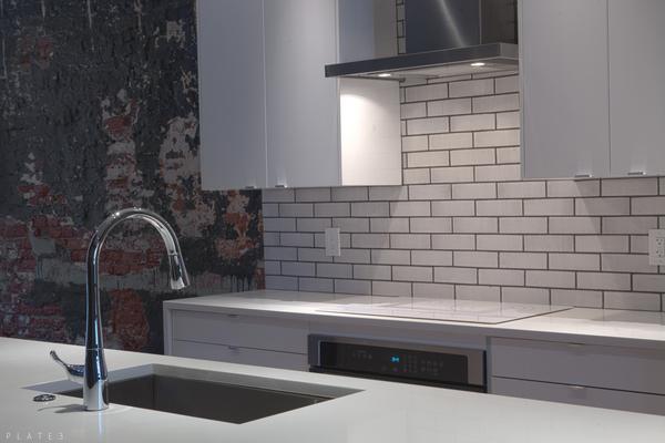 Sleek white kitchen with subway tile and quartz counter tops.