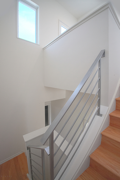 A 50' tall boxed staircase with silver powder-coated railings extends throughout the house.
