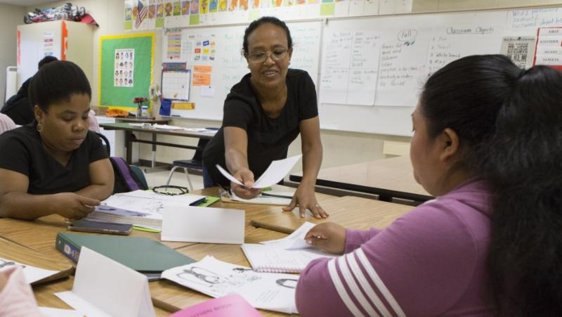 Yordanos Habte hands out practice absence slips to her classmates at Fruitvale Elementary School in Oakland, California on Oct. 1, 2018. She is a student in a family literacy class at her child's school. The class help parents learn skills, such as writing notes to their children's teachers.