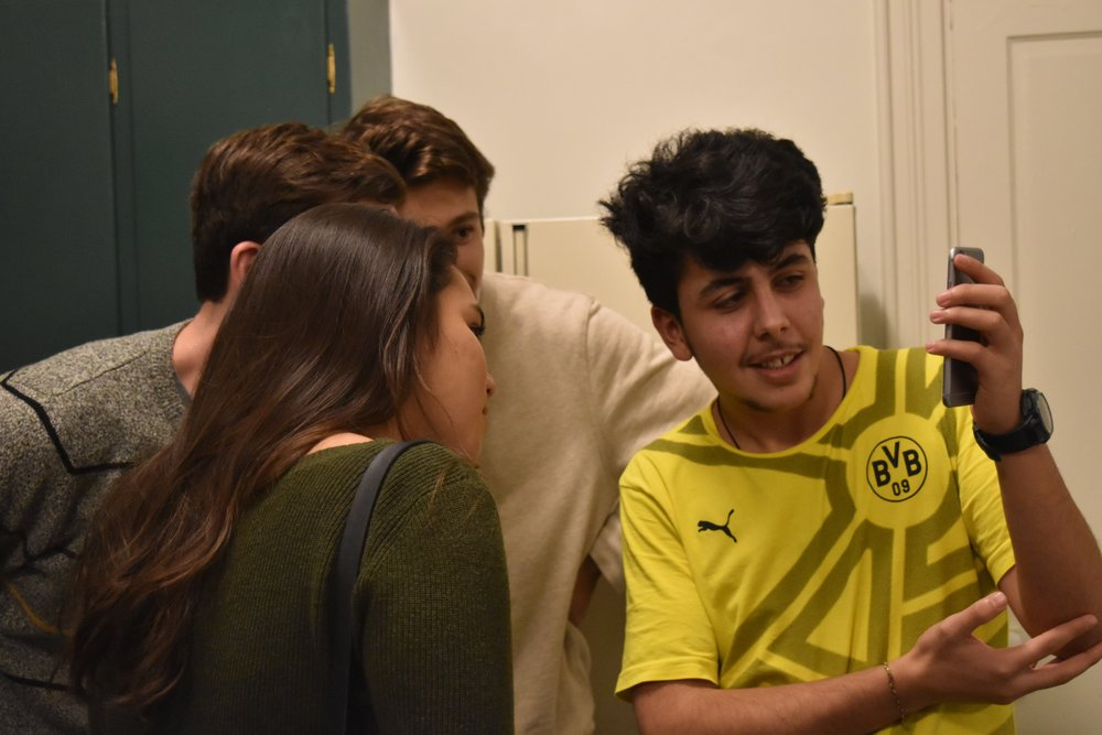 A member of a refugee family shows us a video on his phone. The Environmental Migration Lab group met this family in a Fall 2018 event hosted by  Experience Bridge , which pays Lancaster-based refugees to share their stories along with cuisine from their home countries.